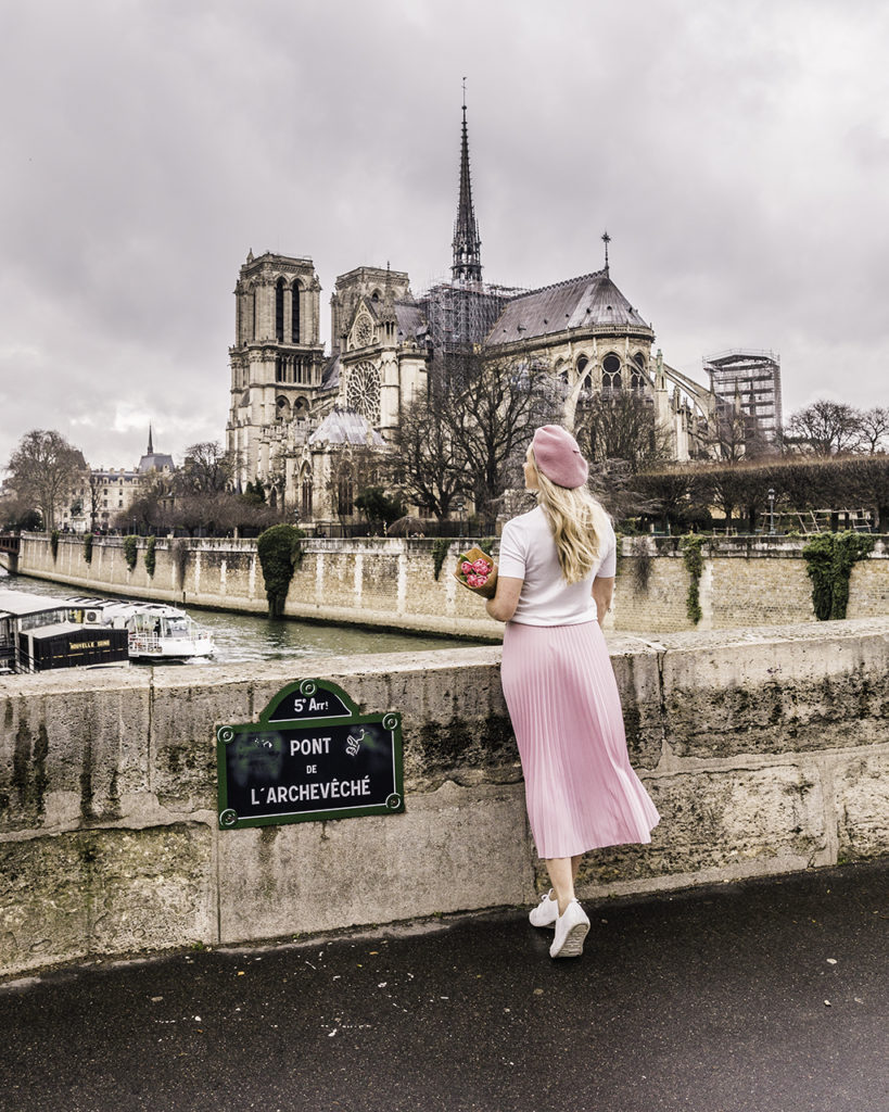 Woman standing at the back of Notre Dame Cathedral in Paris