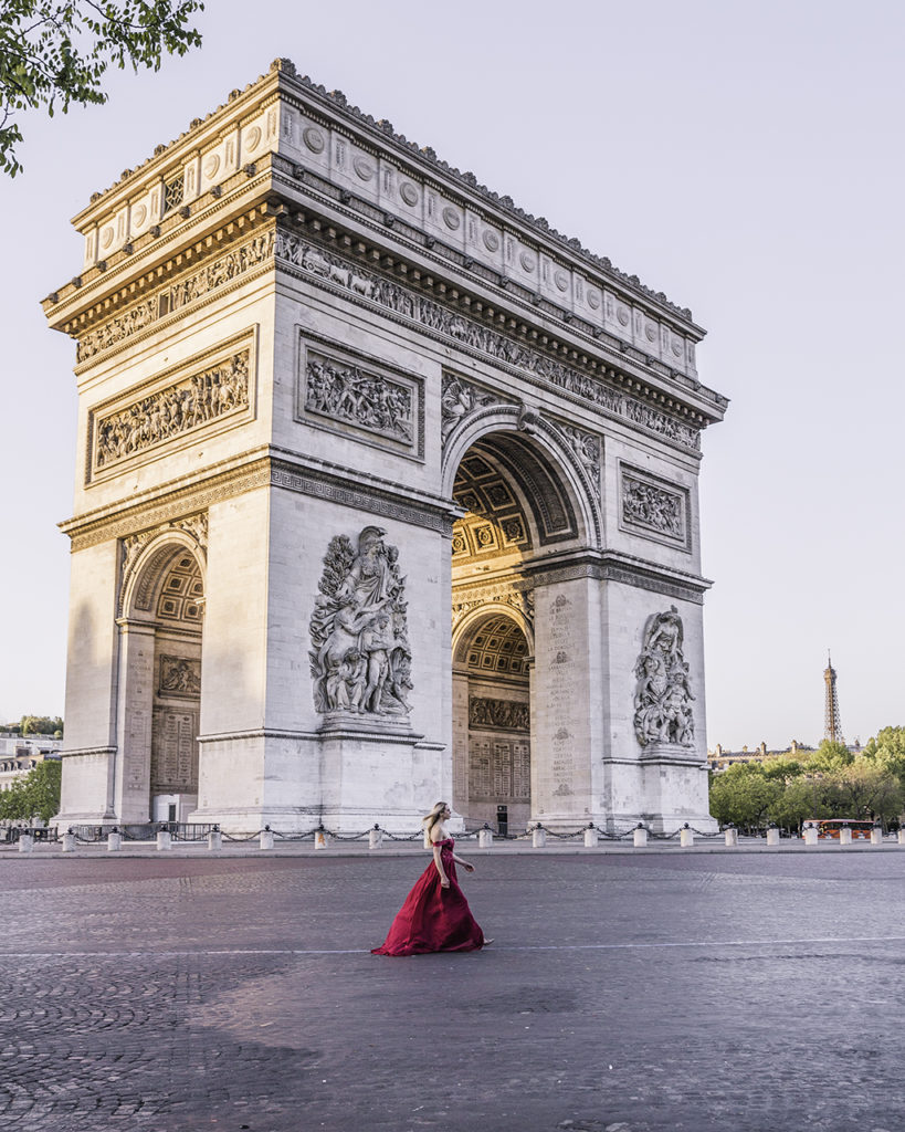 Woman walking in front of Arc de Triomphe at sunrise