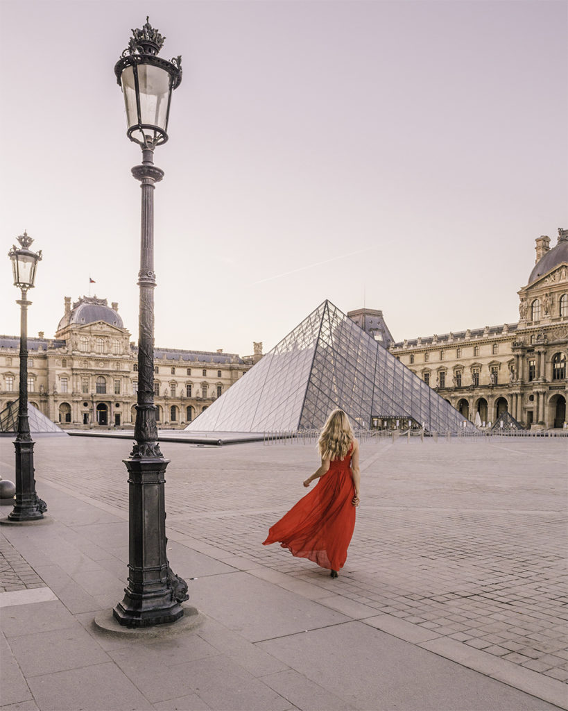 Woman walking in the courtyard of the Louvre museum