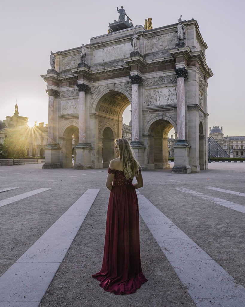 Woman standing in front of Arc de Triomphe du Carrousel at sunrise