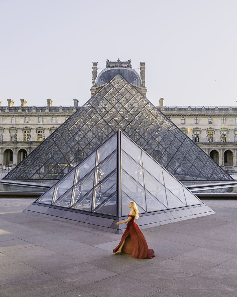 Woman walking in front of the pyramids in the Louvre museum