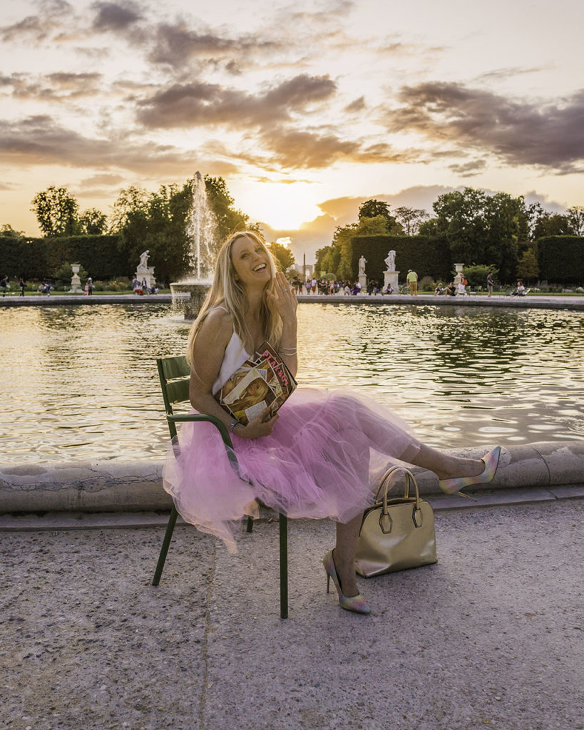 Woman sitting in front of the fountain of the Tuileries gardens at sunset