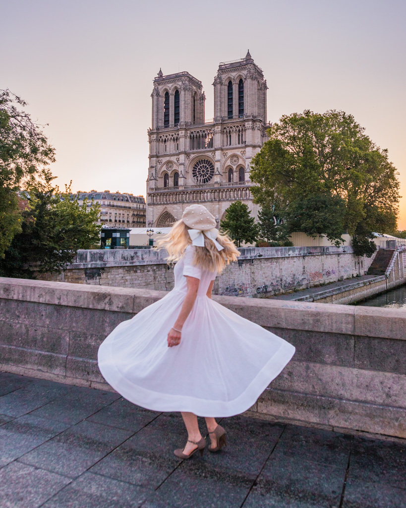 Woman standing in front of Notre Dame Cathedral in Paris